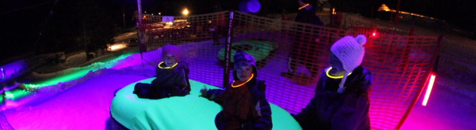 Two snow tubers with glow in dark necklace wait at top of Cosmic Tubing run in 2-man turquoise tube beneath neon lights