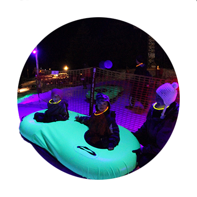 Three youngsters all wearing glow in the dark necklaces await their turn to go down the Cosmic Tubing hill at Mt. Hood Skibowl