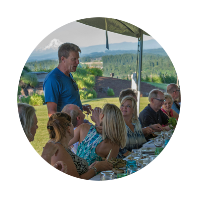 Guests at long outdoor table enjoy summer Dinner in the Field meal as they talk with winemaker of Pete's Mountain Vineyard