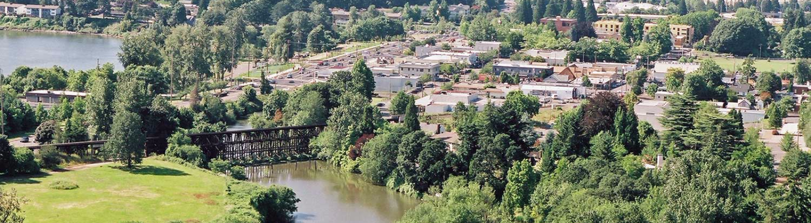 Downtown Milwaukie aerial view with Kellogg Lake forefront, Willamette River to the left and Portland high-rises on horizon.