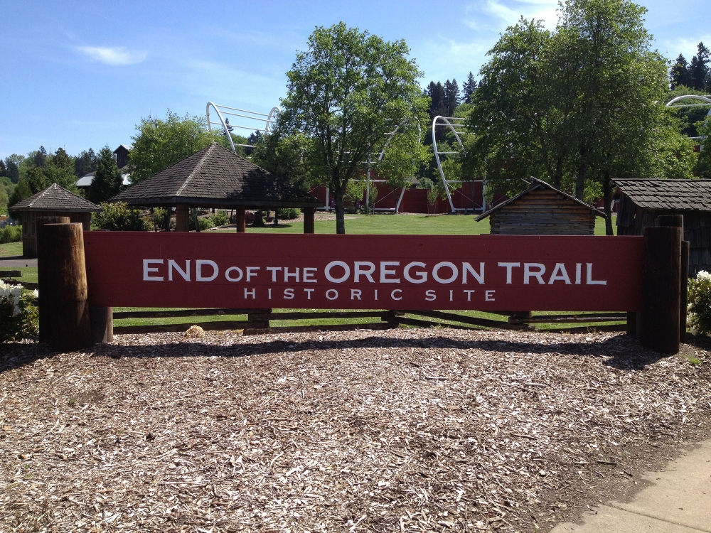 End of the Oregon Trail Historic Site large wooden entrance sign with metal covered wagon bonnet frame in background