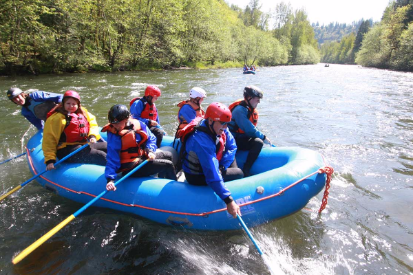 Six rafters and eNRG Kayaking guide in blue inflatable raft dip their oars in the Sandy River and begin their whitewater trip