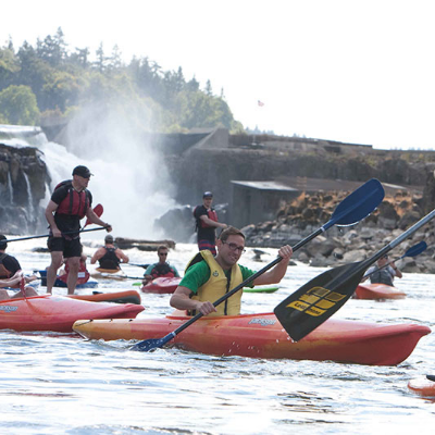 Female on a stand-up paddleboard and kayakers behind her paddling near Willamette Falls in Oregon's Mt. Hood Territory.