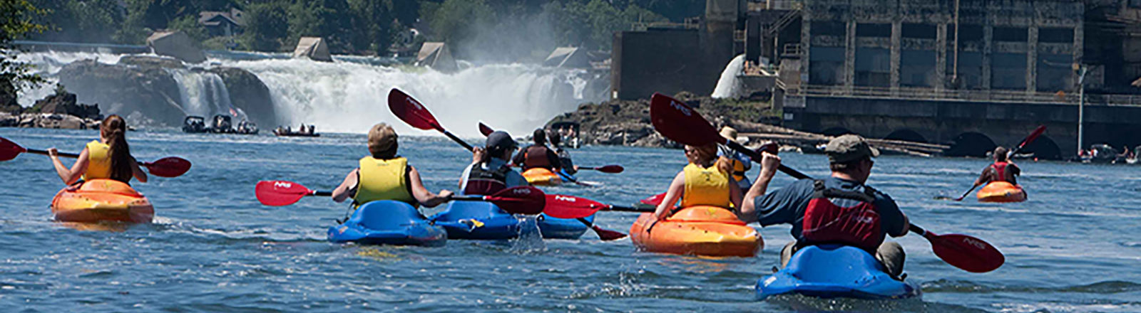 Group of kayakers paddle towards Willamette Falls' rushing waters of the Willamette River in Oregon's Mt. Hood Territory.