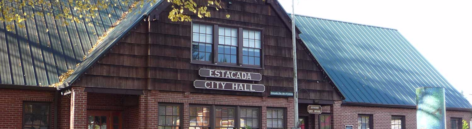 Autumn leaves cover the lawn of the Estacada City Hall, a 2-story wood shake and red brick building
