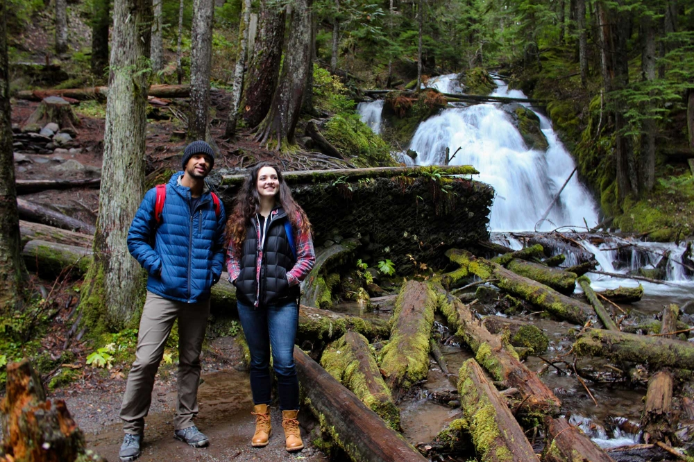 A couple hiking in the Mt. Hood National Forest pause to enjoy the view before them with Little Zigzag Falls in background