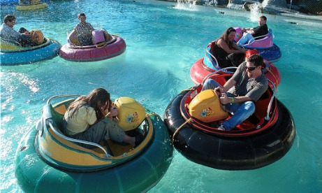 Dads and kids in seven bumper boats having fun bumping others at Family Fun Center and Bullwinkles Restaurant in Wilsonville