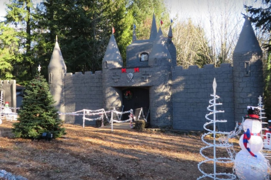 Large gray castle display with snowman and spiral trees which are lighted at night at Christmas Fantasy Trail at Wenzel Farm