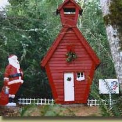 Santa and a little red house with low white picket fence display at Wenzel Farm's Christmas Fantasy trail out of Oregon City
