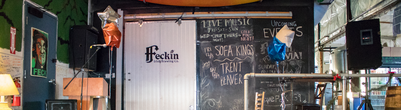 Feckin Brewery & Smokehouse tasting room tables and musical stage with large wall chalkboard of live music listings