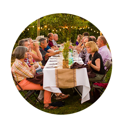 Strings of white lights on a vineyard's end poles add to the festive outdoor atmosphere of diners at a Dinner in the Field.