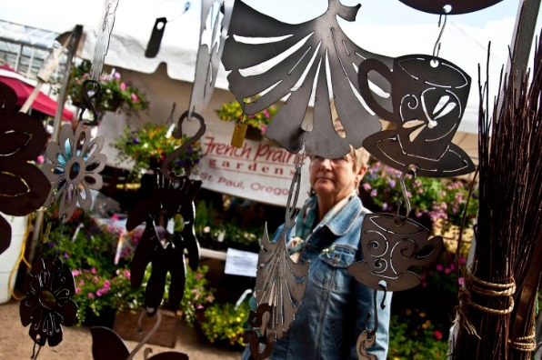 Shopper admires dragonfly coffee cups, ginkgo leaves and other shapes of metal garden art at GardenPalooza spring sale event