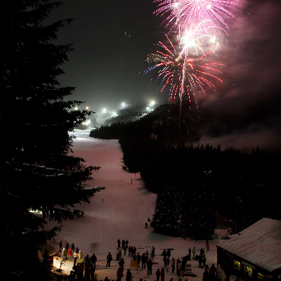 Crowd gathered near the lodge at bottom of ski run as bursts of fireworks shoot up into the night sky at Mt. Hood Skibowl