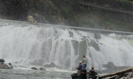 Water mist fills the air at Willamette Falls as three fishermen in boat cast their lines at the base of the falls.