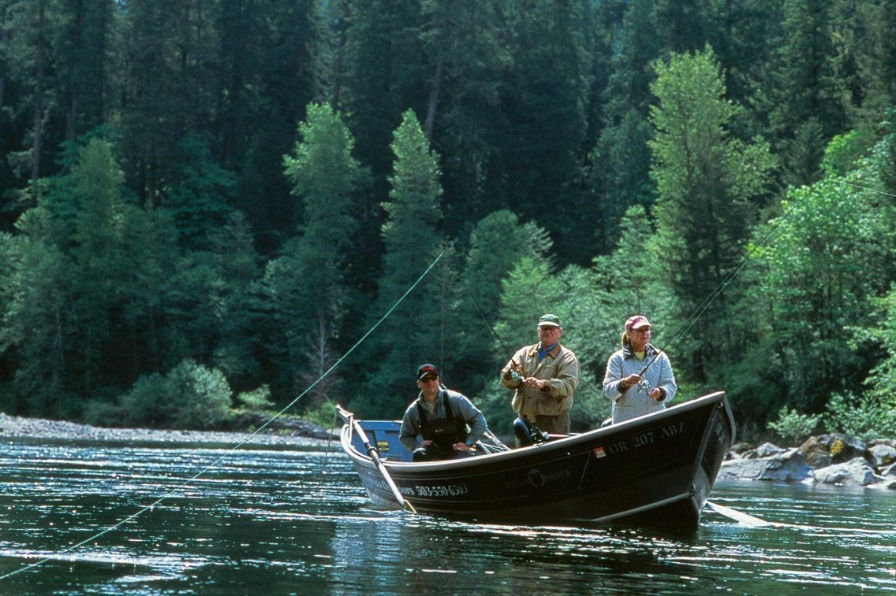 Couple cast their lines from drift boat during guided fishing trip on the Sandy River.