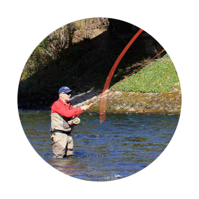 Fisherman in red shirt and waders using bright orange line on his reel stands in middle of Sandy River and casts his fly