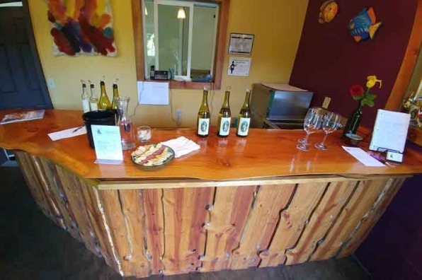 Wooden bar at Forest Edge Vineyard tasting room with bottles of wine, cheese and wine glasses.