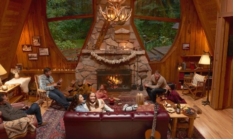 Families relax with hors doeuvres around stone fireplace in great room at Forrest Lodge as one plays music on his ukulele