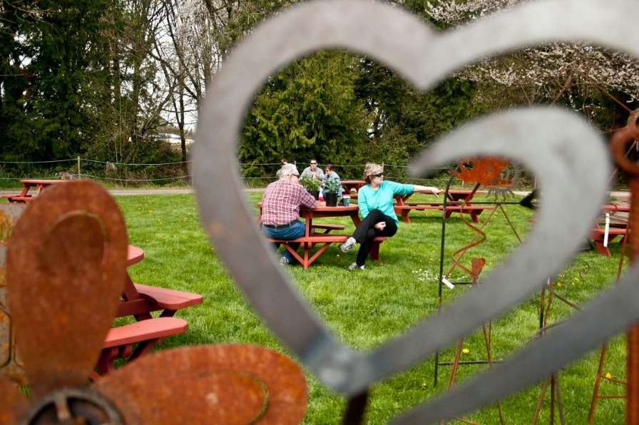 Couple attending GardenPalooza plant sale sitting at picnic table seen through a stainless steel heart piece of garden art