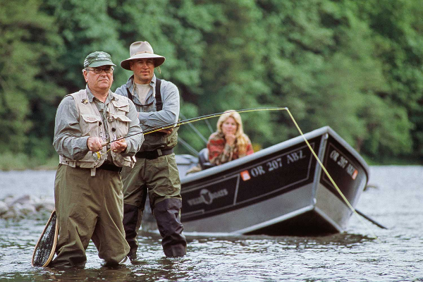 Flyfisherman in waders and fishing vest and guide are standing in Sandy River while fisherwoman remains in drift boat