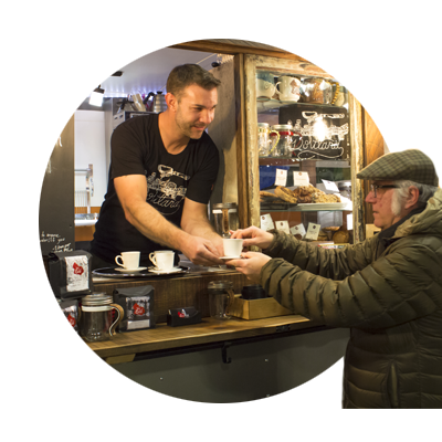 Barista hands a gentleman customer a cup of freshly brewed coffee from his food cart at Happy Valley Station