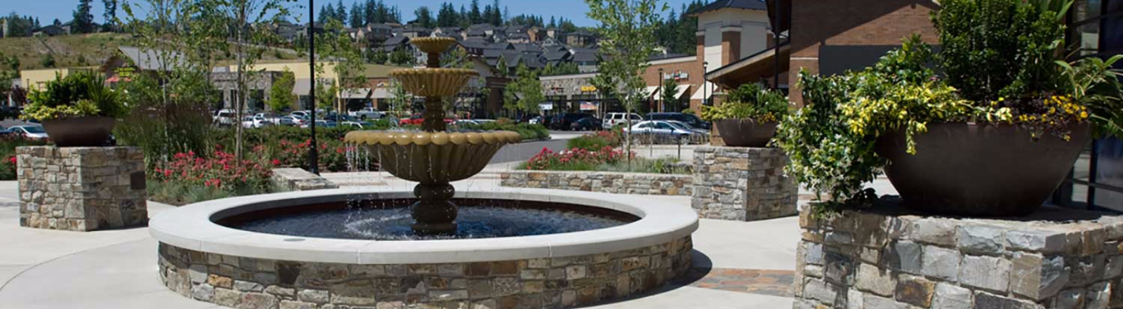 Three tier water  fountain cascading into a circular pool on the open plaza among the businesses at Happy Valley Town Center.