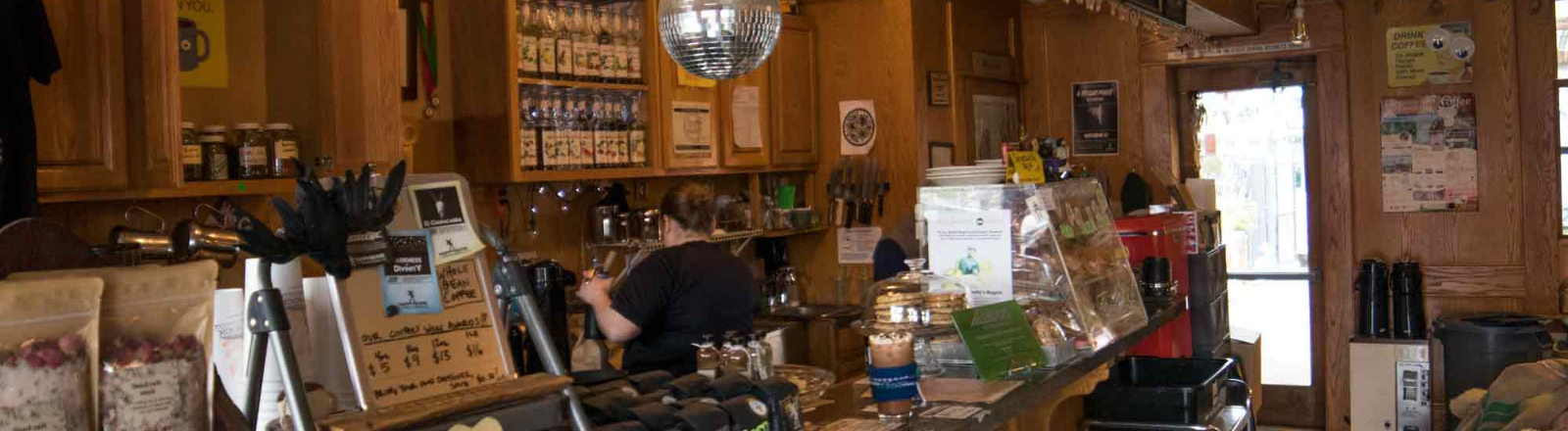 Interior counter with 1 lb. bags of coffee, flavored syrups and pastries with barista making a drink at Gladstone's Happyrock Coffee