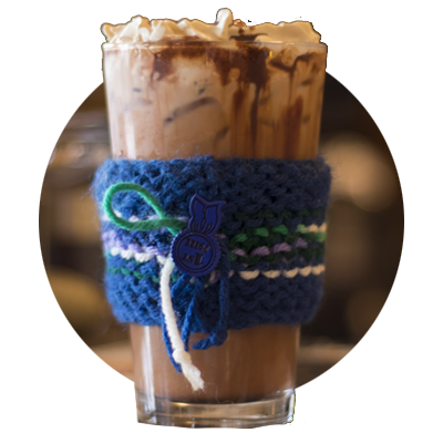 Tall glass of Happyrock iced coffee with blue knitted sleeve holder around glass
