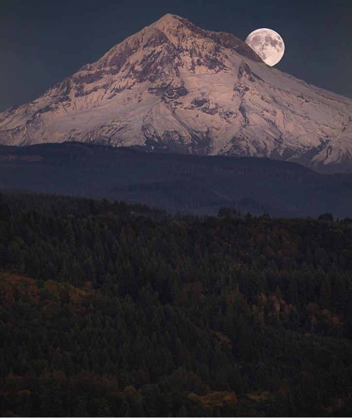 valley in the forefront and giant view of Mt. Hood with snow and full harvest moon peaking out behind the mountain