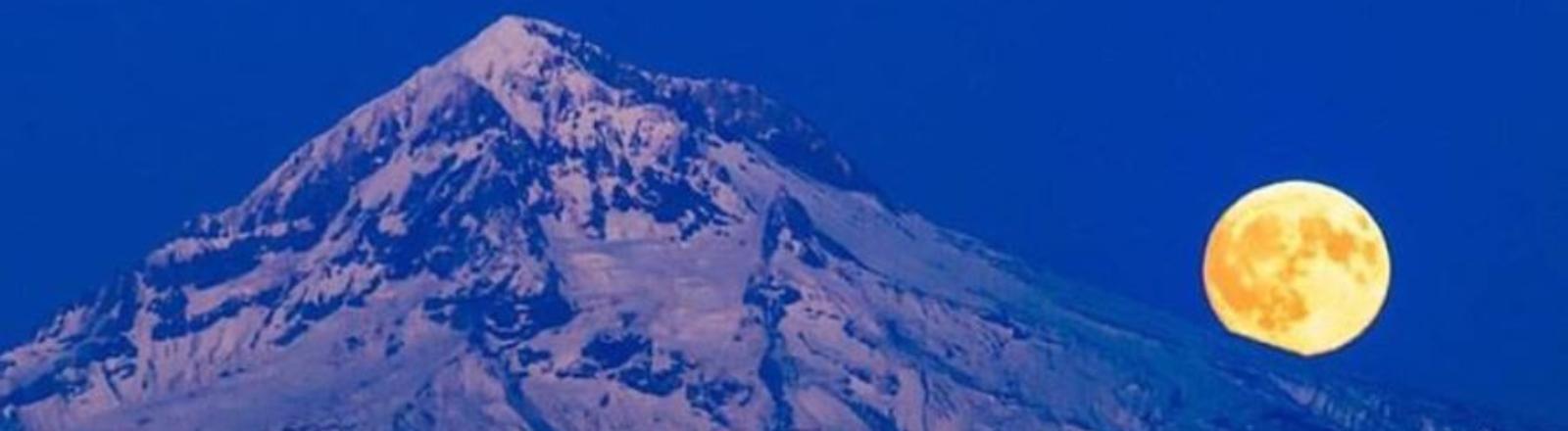 Harvest full moon glowing yellow and orange in a deep dark blue sky rises from behind Mt. Hood in Oregon's Mt. Hood Territory