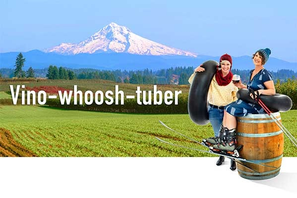 Superimposed over farmland & Mt. Hood are two females with inner tubes and one is sitting on wine barrel wearing skis with glass of wine. Copy reads VinoWhooshTuber.