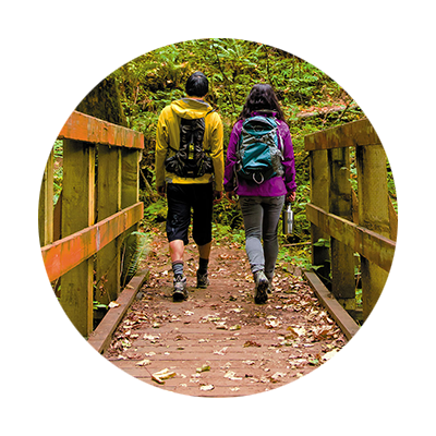 Couple with daypacks walk across footbridge covered with leaves to begin a hike in the Molalla River Recreation Corridor.