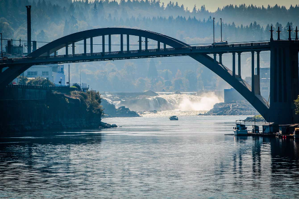 Willamette River with view of Willamette Falls and boat in distance framed under the historic 1922 Arch Bridge