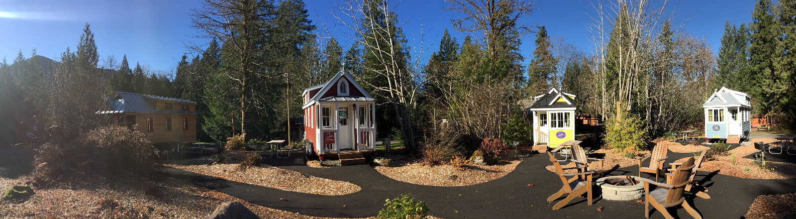 Panorama of four tiny house vacation rentals, and chairs around fire pit area at Mt. Hood Tiny House Village in Welches
