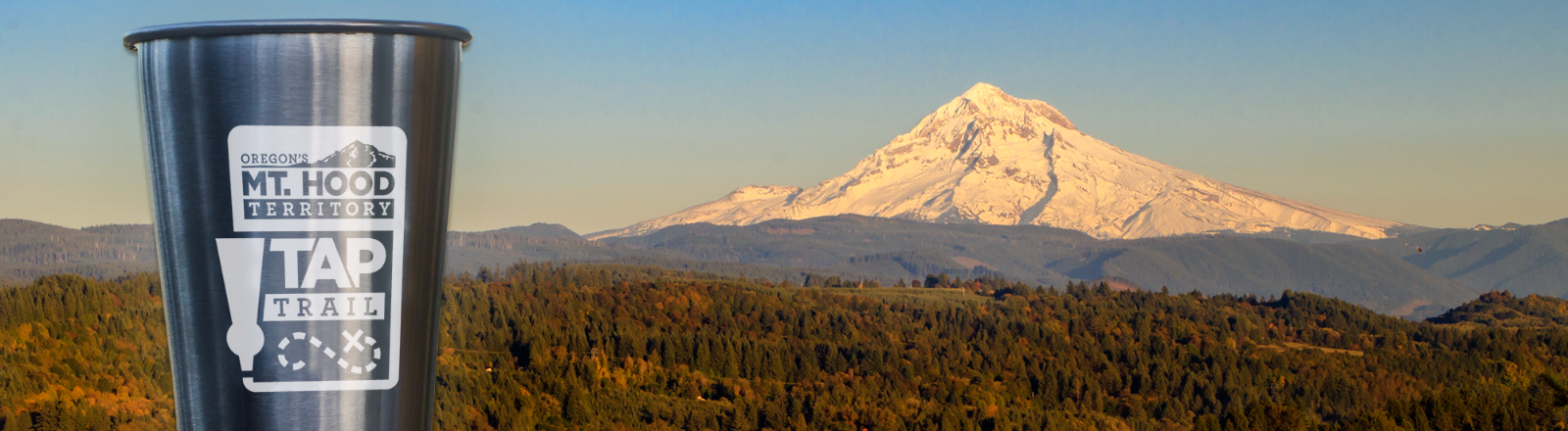 Autumn view of Cascade foothills and Mt. Hood from Jonsrud Viewpoint in Sandy with stainless Tap Trail glass resting on fence post at the viewpoint