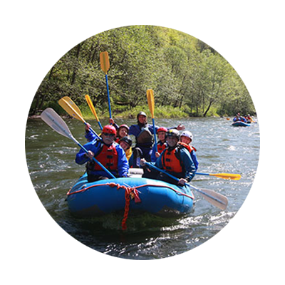 Six helmeted whitewater rafters and their guide lift their paddles as their blue raft floats through the river's ripples.