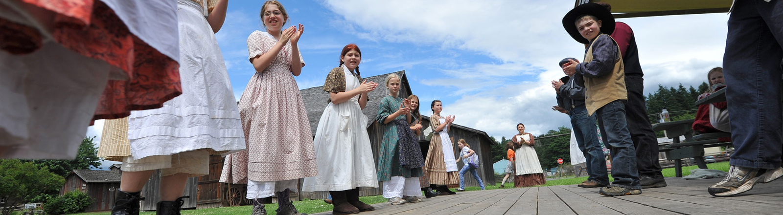 In long dresses and aprons or vests and jeans pioneer chldren reenactors line up for a reel dance at Philip Foster Farm.