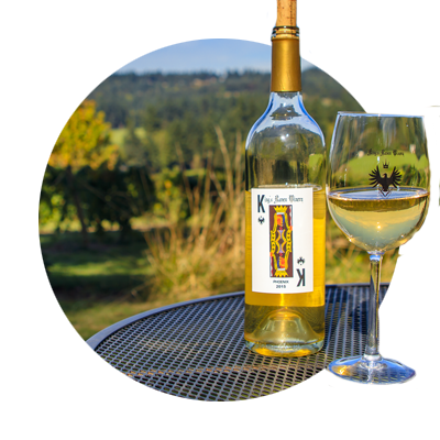 Close-up of bottle and glass of King's Raven Pinot Gris on the tasting room patio table with the vineyard in the background