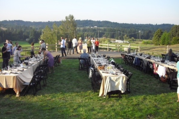 Some guests choose seats at tables set on the lawn as others mingle enjoying libations at King's Raven Winery's farm dinner