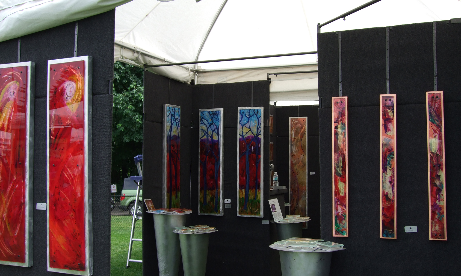 Artists booth of 3 1/2 to 4 ft. high by 6 inches to 1 ft. wide colorful paintings at Lake Oswego Festival of the Arts
