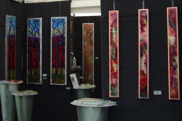 Artist's booth of 3 1/2 to 4 ft. high by 6 inches to 1 ft. wide colorful paintings at Lake Oswego Festival of the Arts.