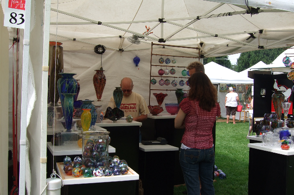 Colorful glass floats, vases, sun catchers and other items in artisan's booth at Lake Oswego Festival of the Arts.