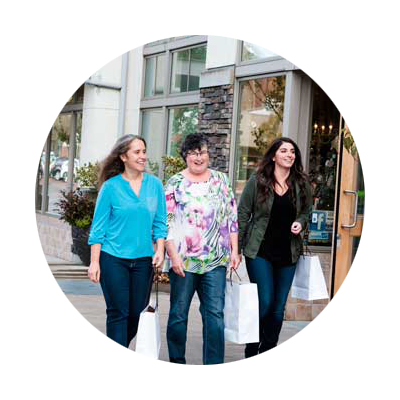 Three girlfriends with filled shopping bags in hand enjoy an afternoon of shopping and dining in Lake Oswego.