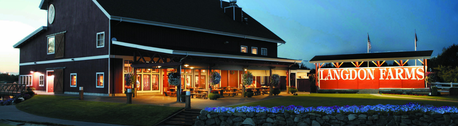 Twilight view of Langdon Farms golf Club's big red barn-like clubhouse and restaurant patio with lit Langdon Farms sign