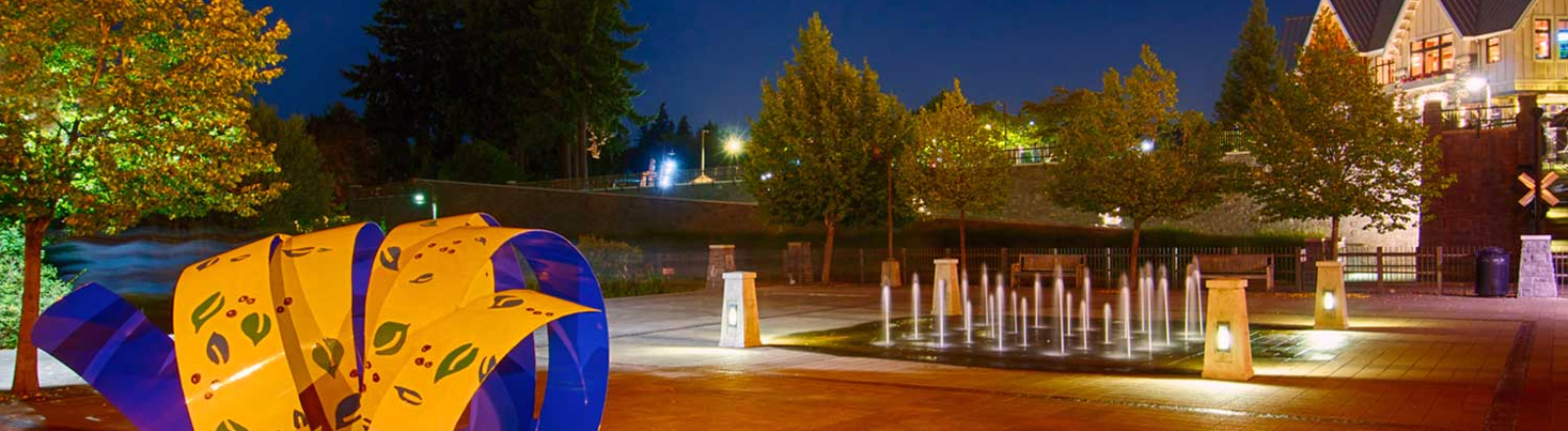 Whimsical Yellow U0026 Blue Metal Sculpture And Interactive Splash Fountain Lit  At Night On Lower Millennium. Lake Oswego