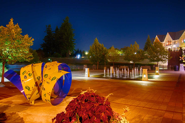 Whimsical yellow & blue metal sculpture and interactive splash fountain lit at night on lower Millennium Plaza in Lake Oswego