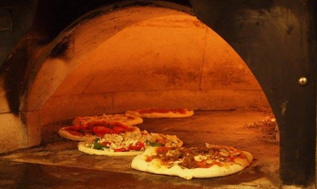 5 pizzas all cooking at one time in wood oven at Oregon Citys Mi Famiglia Wood Oven Pizzeria in Oregons Mt Hood Territory