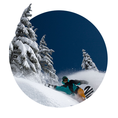 Snowboarder sprays a rooster tail of fresh powder snow as he carves his way around a hillside of snow laden trees