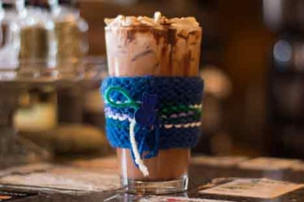 Tall glass of Happyrock Coffee Roasters iced mocha with hand-knitted blue sleeve holder