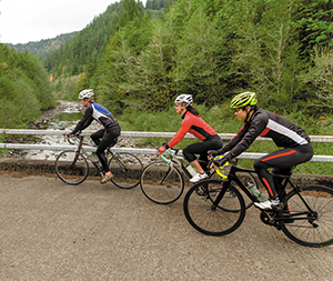 Three bicyclists ride across a bridge over a river
